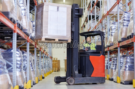man with tablet pc operating forklift