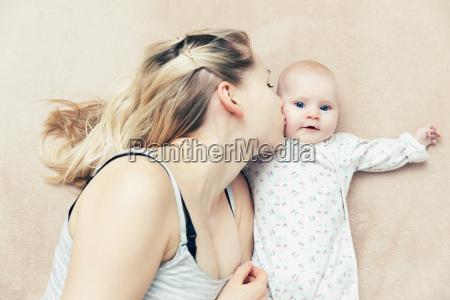 mother kissing her infant baby girl