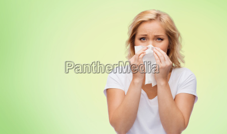 unhappy woman with paper napkin blowing