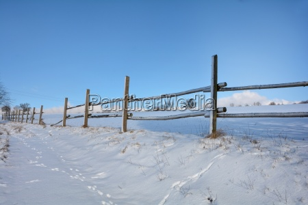 wooden fence in winter with snow
