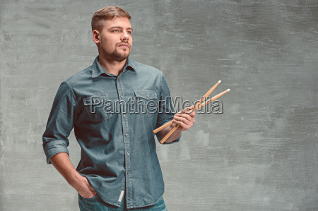 man holding two drumsticks over gray