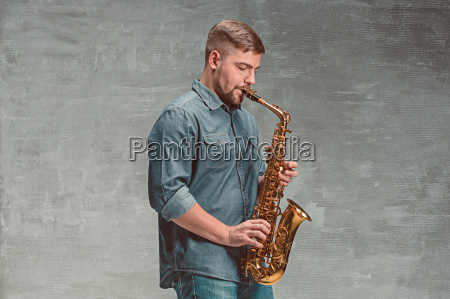 happy saxophonist playing music on sax