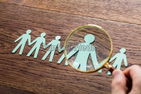 person using magnifying glass on cut
