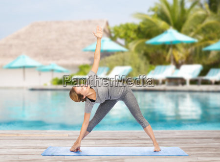 woman making yoga triangle pose on