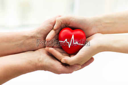 man hand giving red heart to