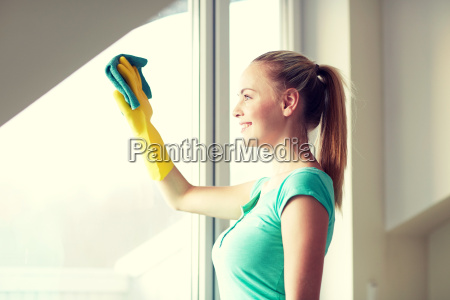 happy woman in gloves cleaning window