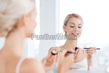 woman with makeup brush and eyeshade
