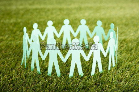 papercut of people chain on grass