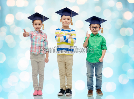 happy children in bachelor hats and