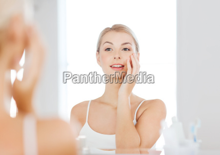happy young woman looking to mirror
