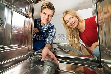 male worker repairing dishwasher in kitchen