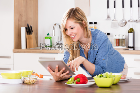 smiling woman using digital tablet in