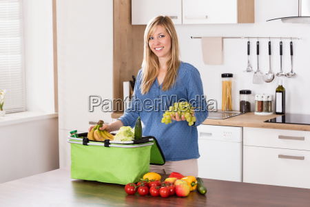 smiling woman removing grapes from grocery