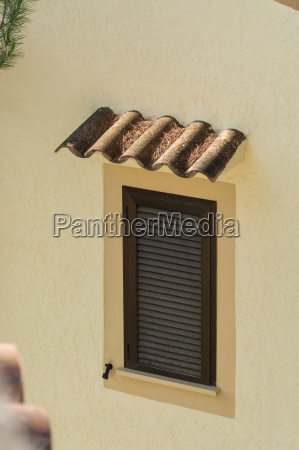 window with brown shutters closed