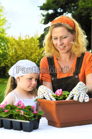 young woman and little girl gardening