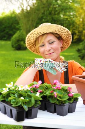 young woman planting flower seedlings gardening