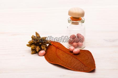 pink pills with orange leaf on