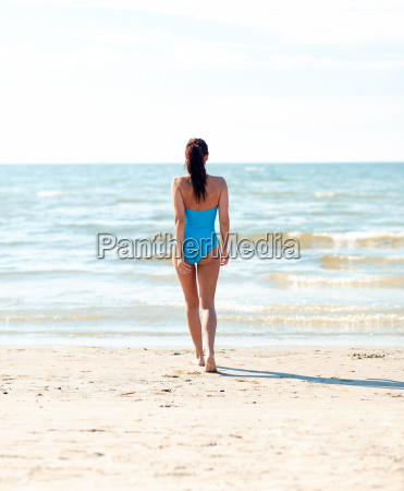 young woman in swimsuit walking on