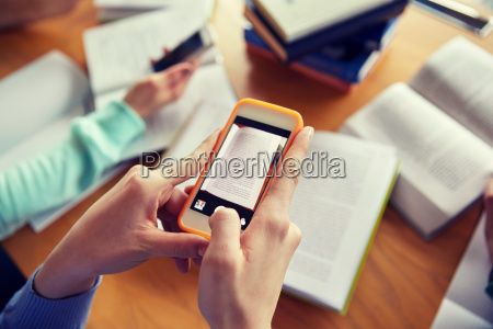 students with smartphones making cheat sheets