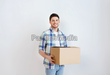 smiling young man with cardboard box