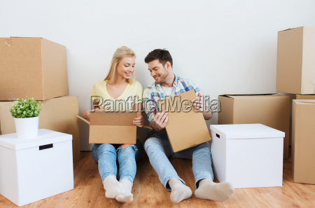 smiling couple with many boxes moving