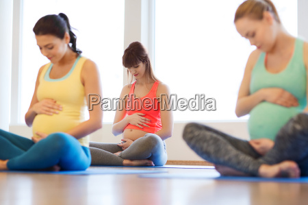 happy pregnant women exercising yoga in