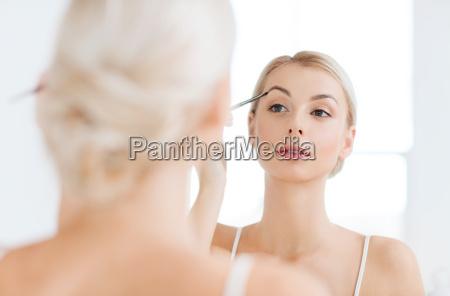 woman with brush doing eyebrow makeup