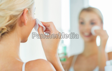 close up of woman cleaning face