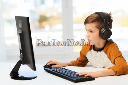 boy with computer and headphones at
