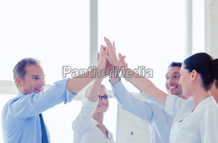 happy business team giving high five