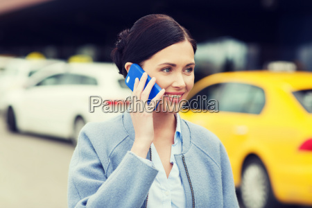 smiling woman with smartphone over taxi