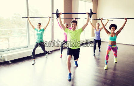 group of people exercising with bars