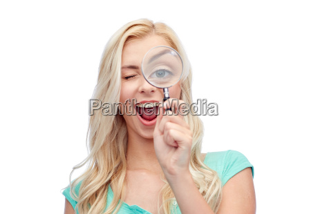 happy young woman with magnifying glass
