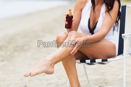 woman spraying sunscreen oil to her