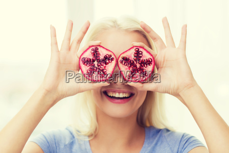 happy woman covering eyes with pomegranate