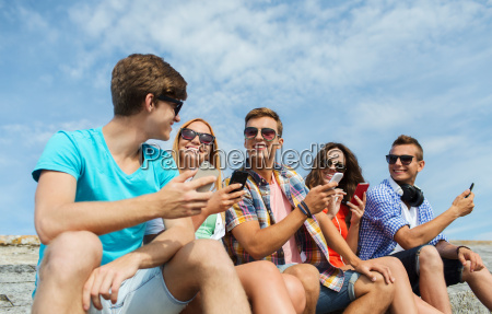 group of happy friends with smartphones