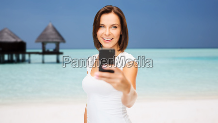 happy woman taking picture by smartphone