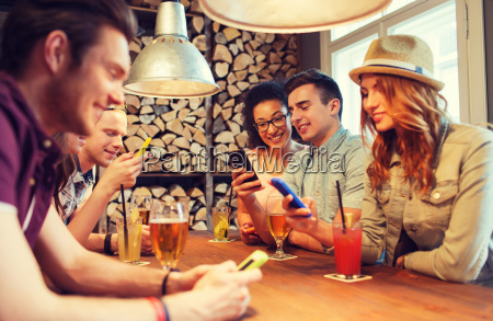 happy friends with smartphones and drinks