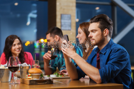 man with smartphone and friends at