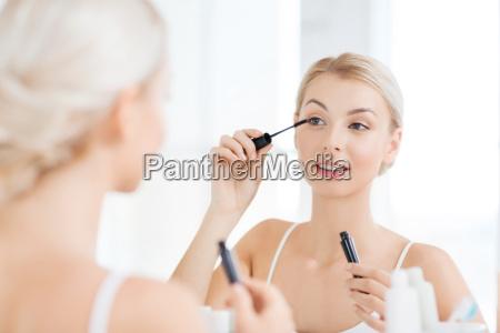 woman with mascara applying make up