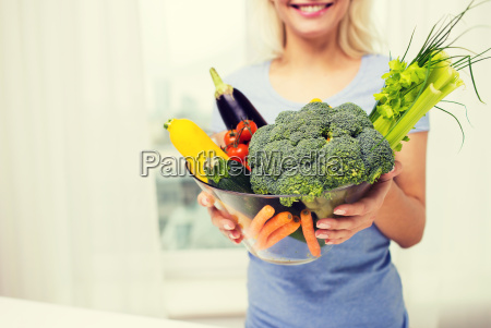 close up of woman holding vegetables