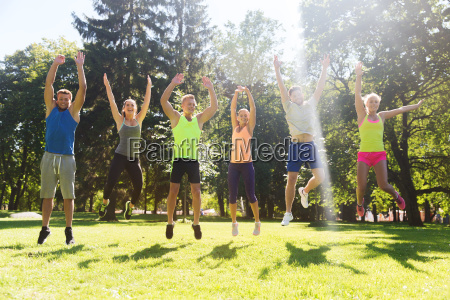 group of happy friends jumping high