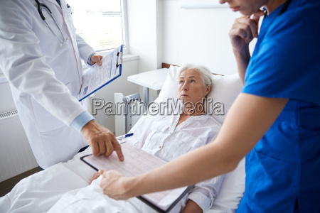 doctor and nurse visiting senior woman