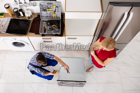 male worker repairing oven using multimeter