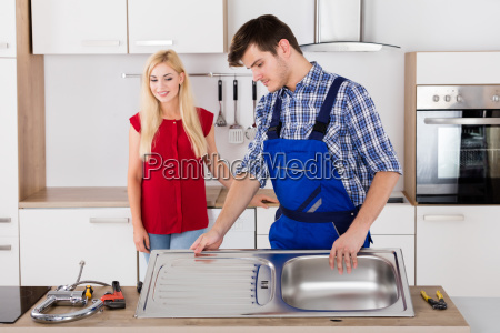 male plumber fixing stainless steel sink