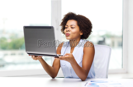 african woman sending kiss to laptop