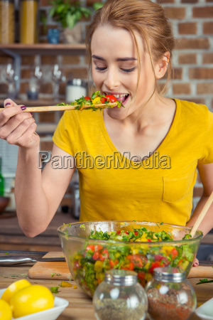 woman tasting vegetable salad