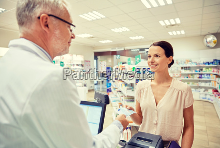 woman, giving, money, to, pharmacist, at - 20054246