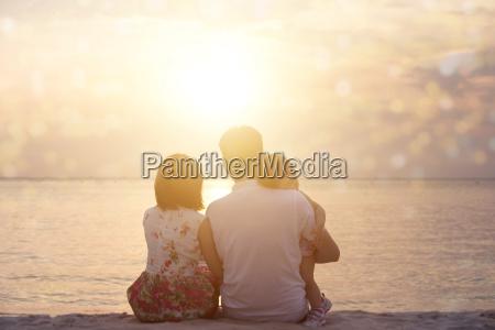 family enjoying sunset view at seaside