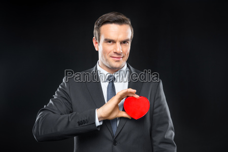 man hoding toy heart